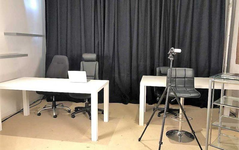A film camera stands in front of white desks and a black hanging curtain.