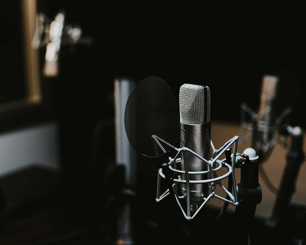 A silver microphone in a recording studio.