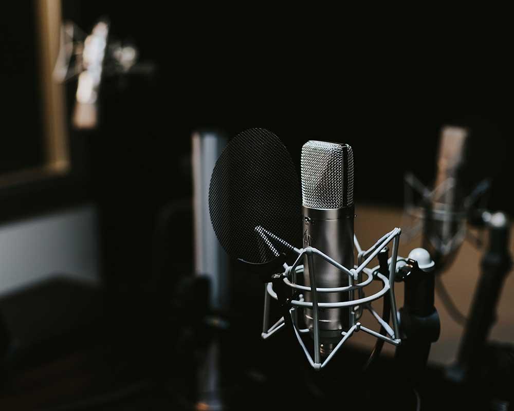 A silver microphone in a recording studio.
