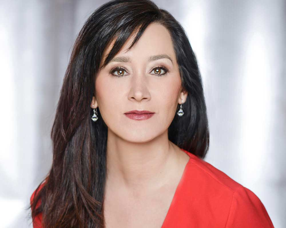 Headshot of woman with long dark hair wearing a red shirt.