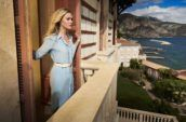 A blonde women stands on a balcony overlooking mountains and a large body of water.